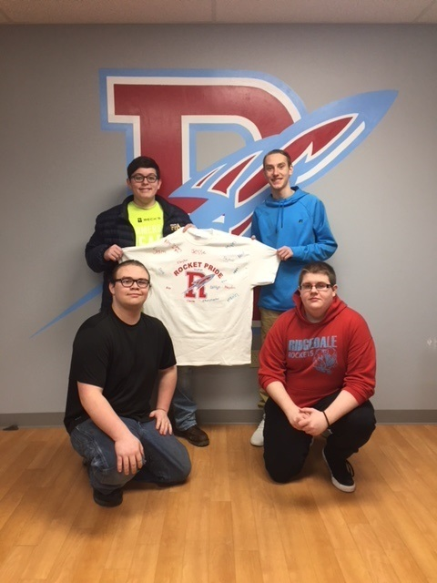 Ridgedale junior's Riley Brown, Jason Smith, Chris Pinnick, and Payton Breece displaying the December student of the month shirt, Jacob Matteson December Student of the month