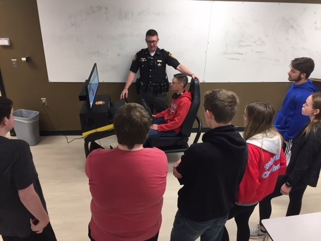 Officer Zempter working with RHS students in the distracted driving simulator